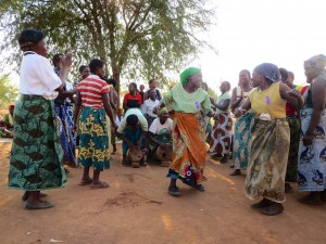 Getting down to business. This is a typical scene in a community meeting where they often share their objectives in song and dance form.